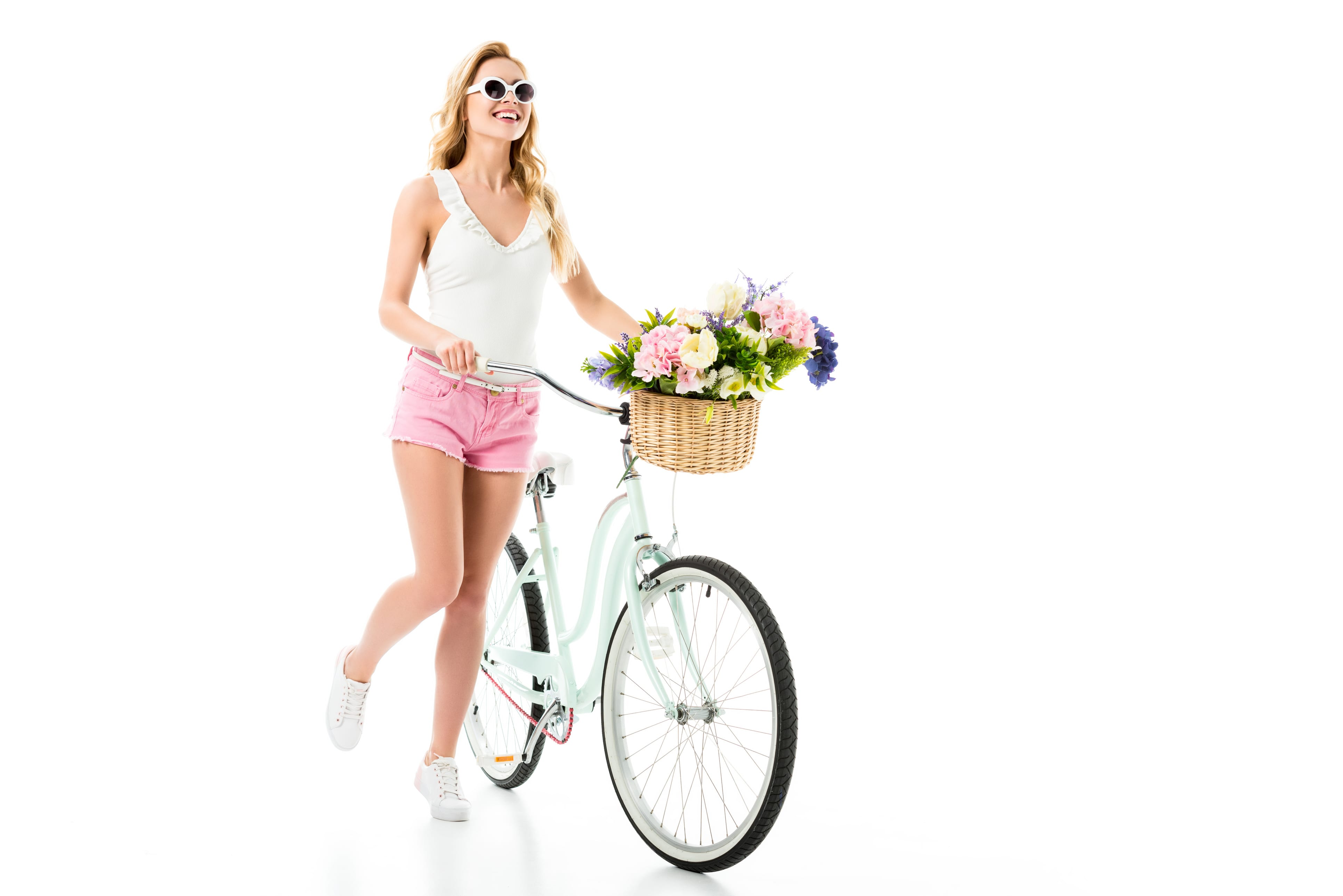 Young girl in sunglasses standing by cruiser bicycle