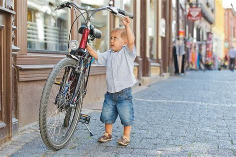 photo of a kid with a bike that is too big