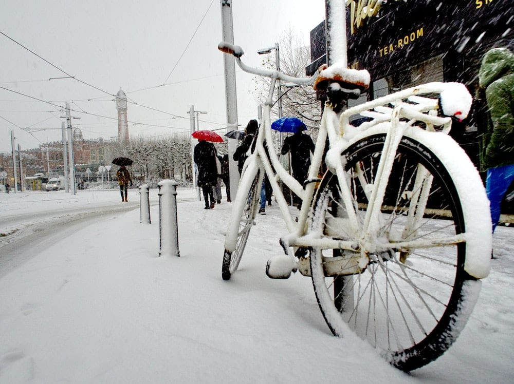 bike cover with snow parked on road