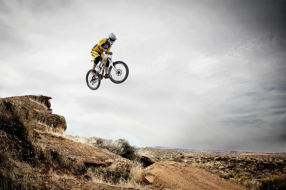cyclist leaping over mountain