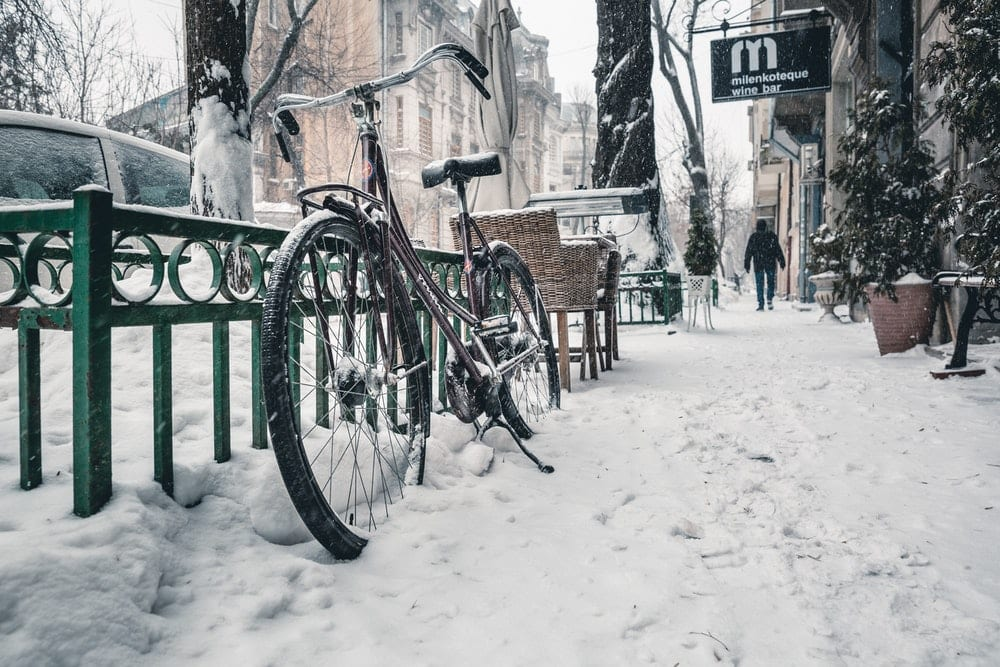 parked bicycle on street in snow