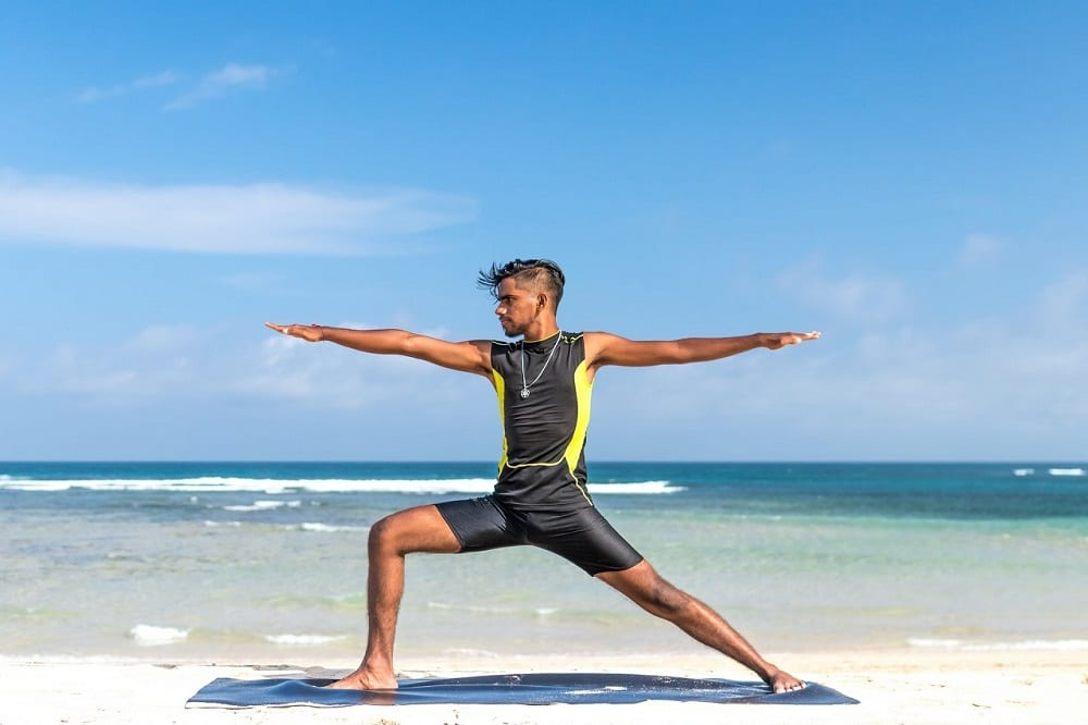 man practice yoga on the beach during day time