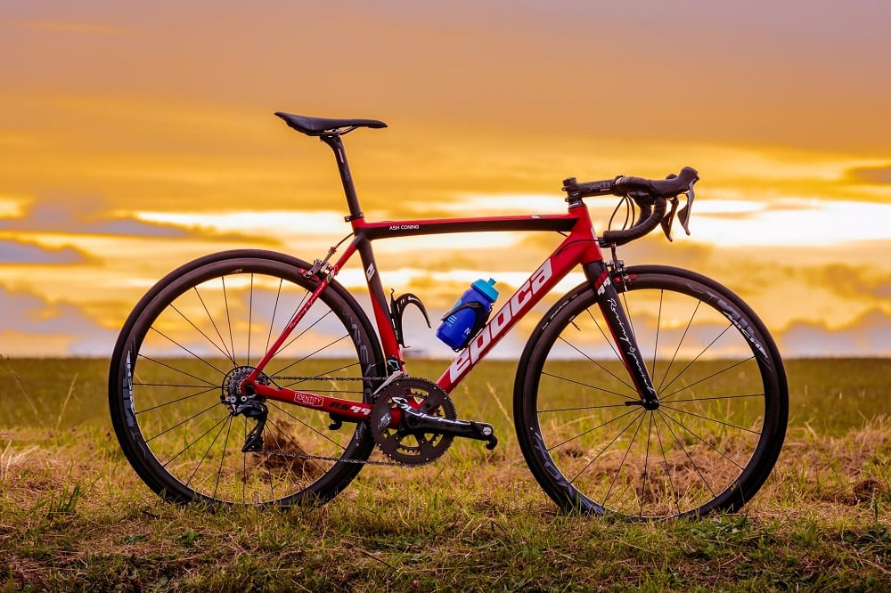 red road bike during sunset on green grass