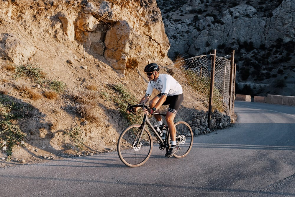 man cyclist pedaling on a road bike outdoors in sun set Road Bikes Vs Hybrids