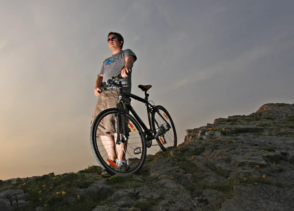 man with hybrid mountain bike on a rocky hill